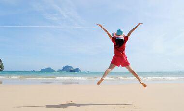 AL Frau macht Freudensprung am STrand Illu Shutterstock