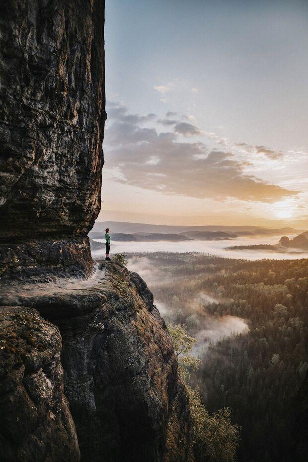 Side View Of Woman Standing On Rock Against Sky During Sunset